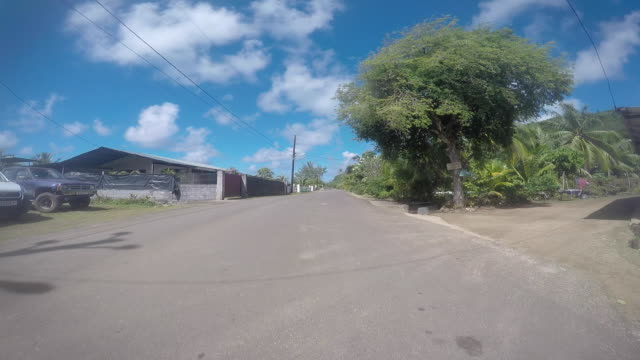 drivers pov, road goes through a village - tahitian culture stock videos and b-roll footage