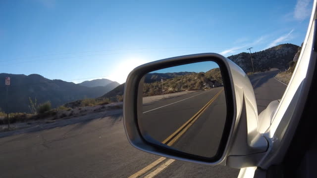 drivers view through side mirror on a curvy mountain road late afternoon - angeles national forest stock videos and b-roll footage