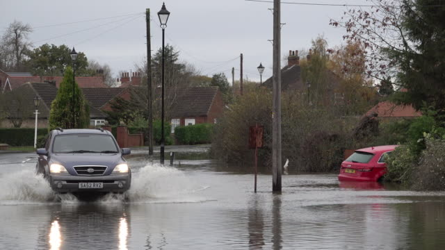 a 4x4 drives past a submerged car on a flooded road as the south yorkshire village for more rain - driving stock videos & royalty-free footage