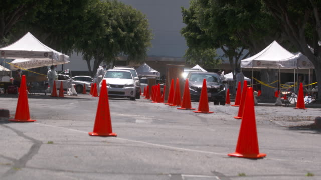 vidéos et rushes de a drivethrough covid19 testing site in los angeles is visited by a long line of motorists taking testing samples through the car windows - processus biologique