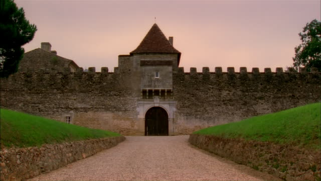 Driveway leading to wall fortification with turret at back entrance to Chateau d'Yquem / Graves, Bordeaux, France