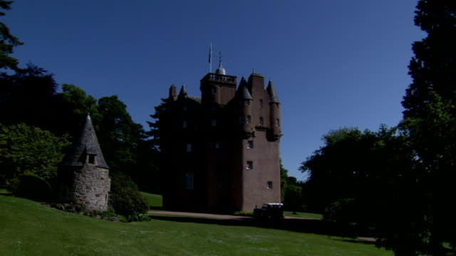 A driveway leads to a castle in the Scottish countryside. Available in HD.