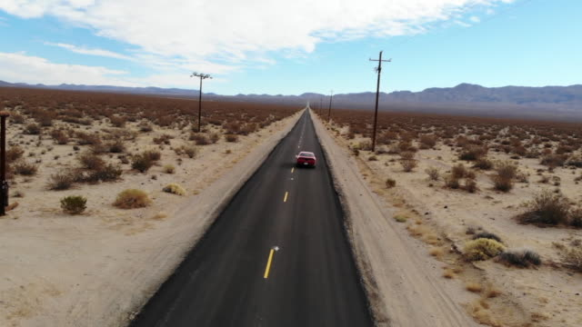 vidéos et rushes de driving a american car in a straight road at the california desert during road trip with cinematic effect. - route 66