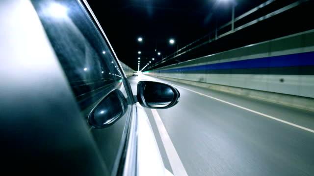 vidéos et rushes de conduire une voiture dans la nuit par le biais de tunnel - rouler ou dérouler