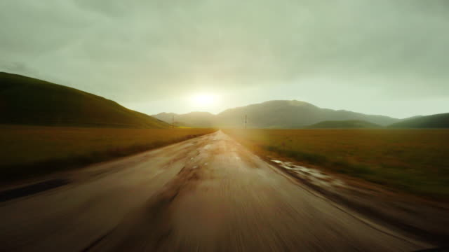 POV Driving a car in a straight road at sunset