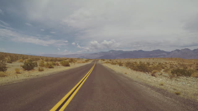 driving a car in death valley scenic roads pov - country road stock videos & royalty-free footage