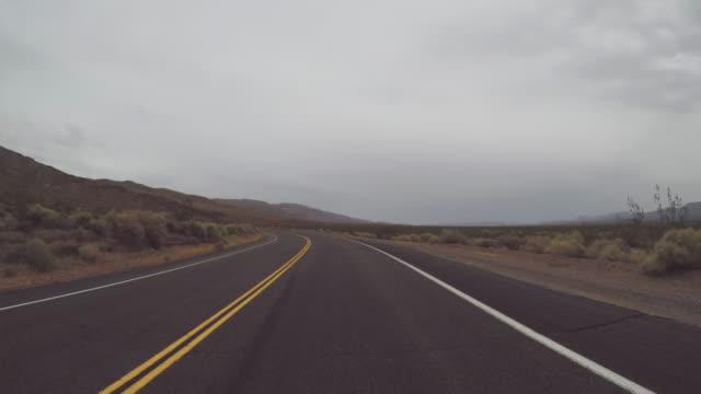 vídeos de stock, filmes e b-roll de dirigindo um carro em estradas panorâmicas do vale da morte pov - pista asfaltada