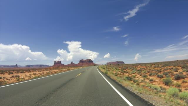 pov driving a car in monument valley - altopiano video stock e b–roll