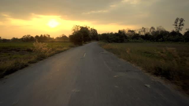 stockvideo's en b-roll-footage met besturen van een auto op een weg bij zonsondergang - als in een droom