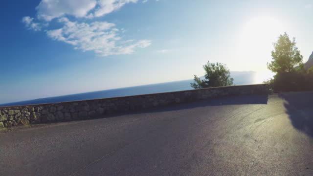 pov driving a car on summer road - strada tortuosa video stock e b–roll