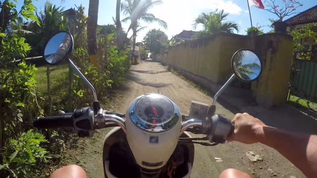 driving a scooter on a dirt road while traveling. - slow motion - indonesia video stock e b–roll