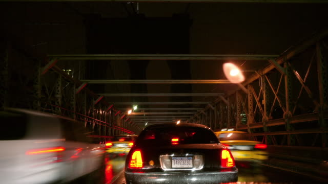 tl pov driving across brooklyn bridge into brooklyn at night/ new york city - taxi stock videos & royalty-free footage
