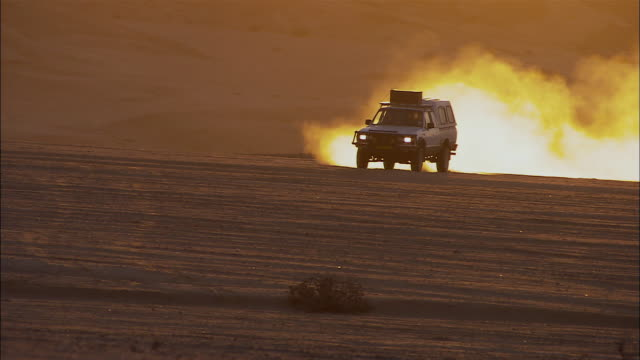 WS TS SUV driving across desert at sunset / Namibia