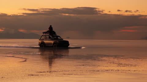 driving across the flooded salar at sunset / salar de uyuni, bolívia - sports utility vehicle stock videos & royalty-free footage