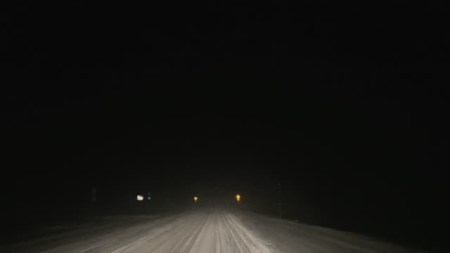 driving along a road at night in a snowstorm while alternating between high and low beams (headlights) - copy space stock videos & royalty-free footage