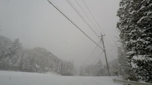 driving along a rural highway during a major winter storm in japan - major road video stock e b–roll