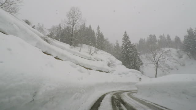Driving along a rural road lined with extremely high snow banks in northern Japan
