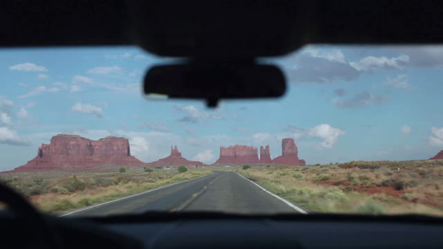 pov driving along an empty stretch of us 163 towards monument valley in the near distance / kayenta, arizona, united states - arizona stock-videos und b-roll-filmmaterial