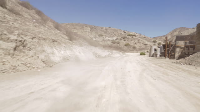 stockvideo's en b-roll-footage met rear pov driving along dirt road past dirt mountains and building structures / santa clarita, california, united states - santa clarita