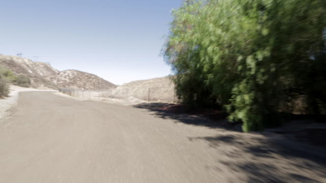 pov driving along dirt road toward mountains / santa clarita, california, united states - santa clarita点の映像素材/bロール