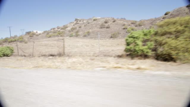 pov driving along mountainside on dusty road / santa clarita, california, united states - santa clarita stock videos & royalty-free footage