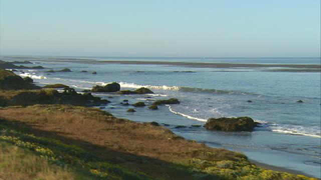 vídeos de stock, filmes e b-roll de side pov driving along pacific ocean beach near san simeon, california, usa - oeste dos estados unidos