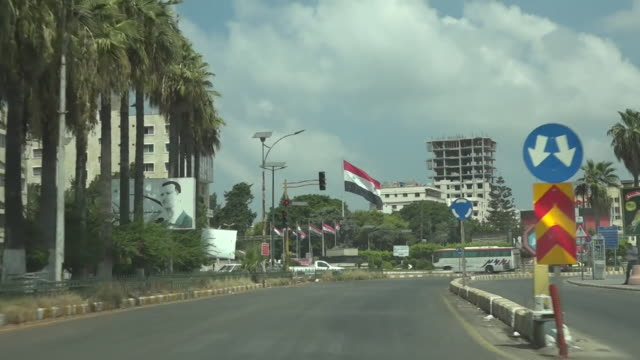 POV driving along road in Tartus a port city in Syria incudes Syrian flags