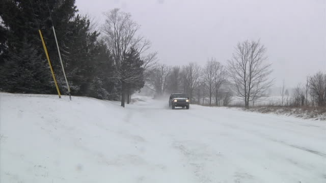 ws suv driving along snow-covered country road during snow storm / chelsea, michigan - slippery stock videos & royalty-free footage