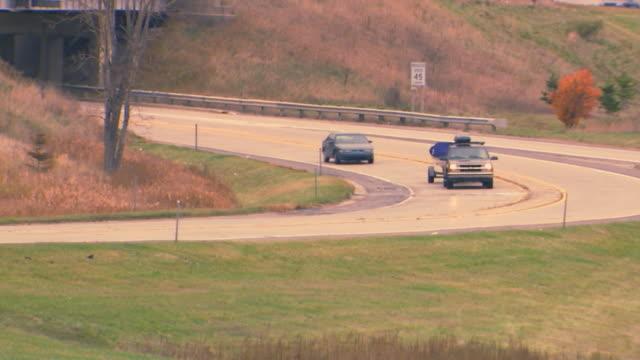 suv driving around corner on highway - trailer stock videos & royalty-free footage