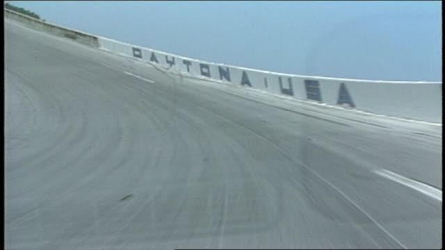 pov of driving around racetrack drivers view in daytona florida - circuito di daytona video stock e b–roll