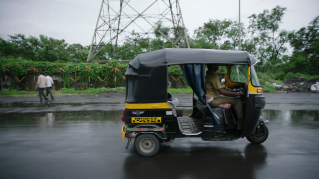 SLO MO. Driving POV as man in pedicab passes by on rainy Mumbai street.