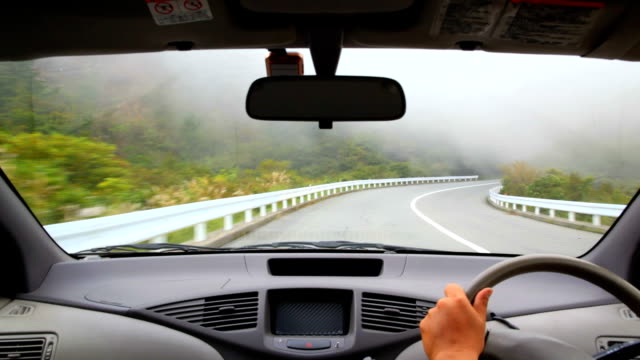 Driving at foggy mountain road.