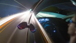 Driving at night on highway, illuminated by blurred street and car lights