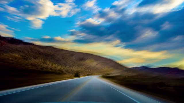 Driving at sunset on desert road