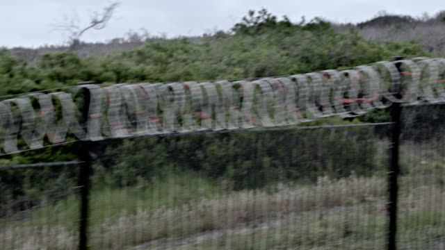 driving by a barbwire fence - shot-1 - chainlink fence stock videos and b-roll footage