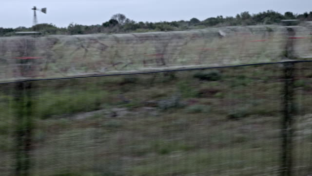 driving by a barbwire fence - shot-2 - chainlink fence stock videos and b-roll footage