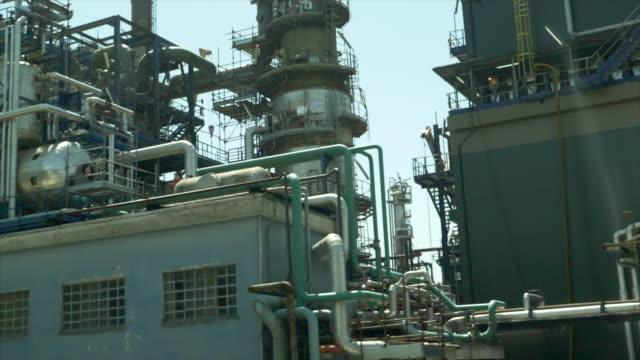 vidéos et rushes de driving by an industrial oil gasoline production refinery. - slow motion - intérieur de véhicule