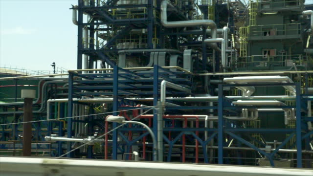 driving by an industrial oil gasoline production refinery. - slow motion - petrol stock videos & royalty-free footage