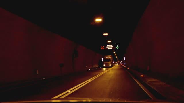 vídeos de stock e filmes b-roll de driving by night through tunnel - sinal de estrada