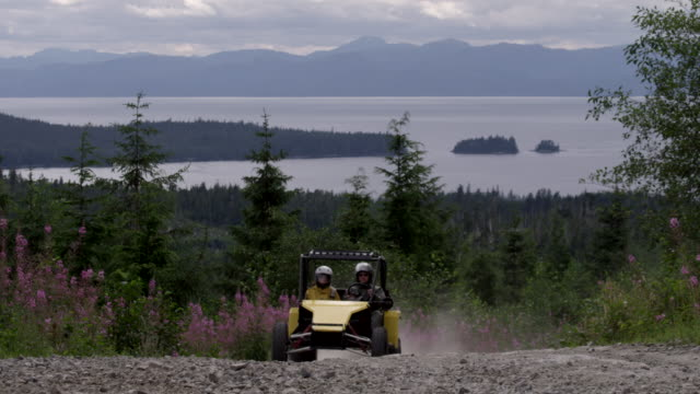 atv driving by with ocean in background - quadbike stock videos & royalty-free footage