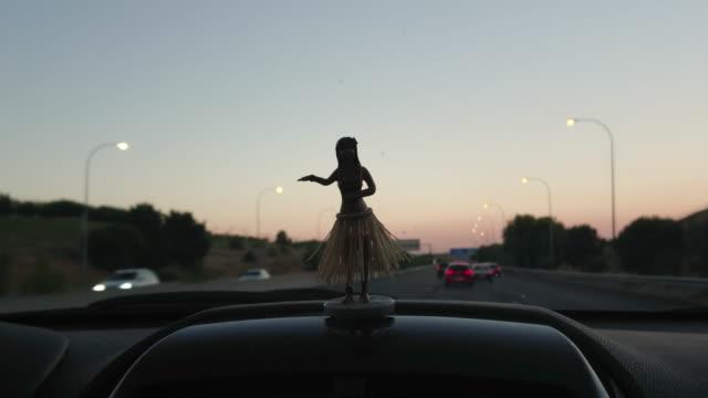 vídeos de stock e filmes b-roll de driving car interior with a hawaian dancer doll in silhouette - boneca