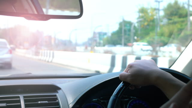 Driving car scene, human hand controlling steering wheel