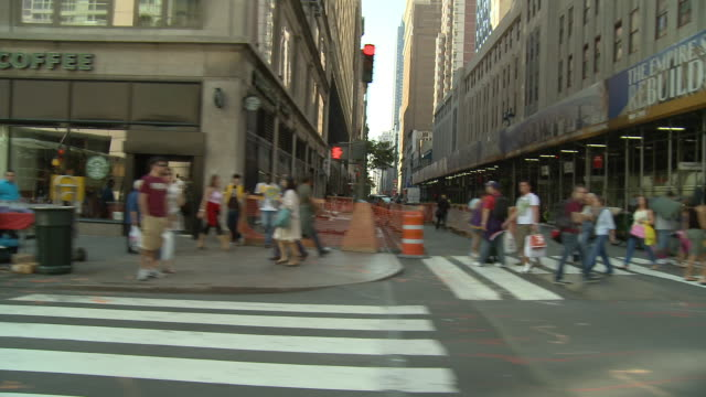 DS Driving down a busy 5th Avenue, passing pedestrians and storefronts / New York City, New York, United States