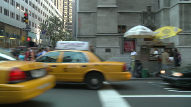 DS Driving down a busy city street, passing pedestrians and storefronts before coming to a stop / New York City, New York, United States