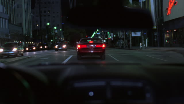 pov driving down a city street behind another car that stops suddenly - following moving activity stock videos and b-roll footage