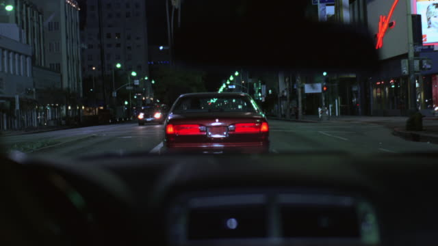 pov driving down a city street behind another car that stops suddenly - tail light stock videos & royalty-free footage