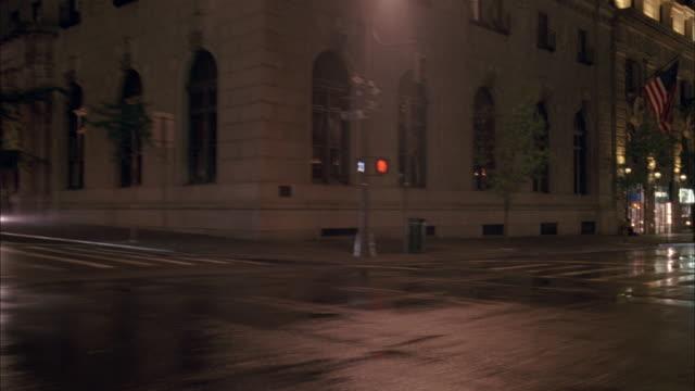 stockvideo's en b-roll-footage met cu driving down a city street in the rain at night - breedbeeldformaat