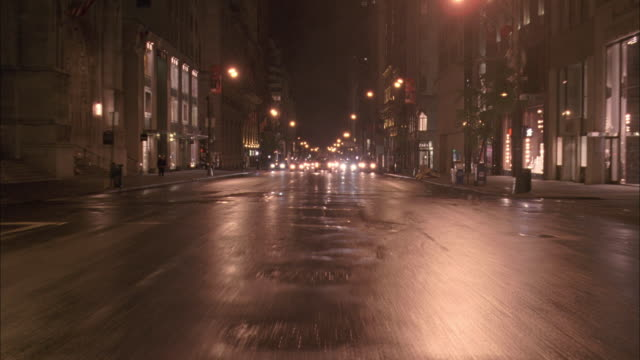 CU Driving down a city street in the rain at night