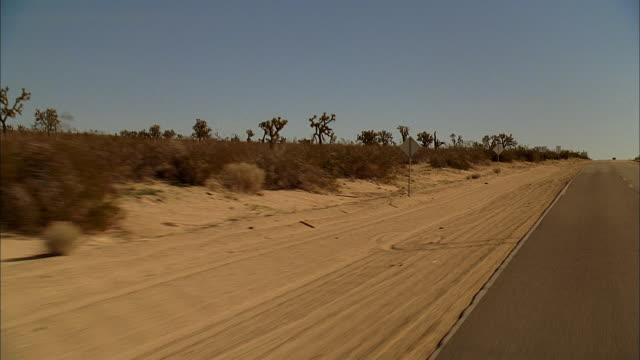 REAR POV Driving down a desert highway