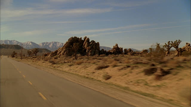 REAR POV Driving down a desert highway with mountains and rocky outcroppings